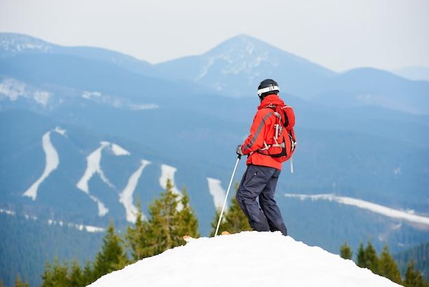 Achteraanzicht van mannelijke skiër genieten van op de top van de helling in skigebied