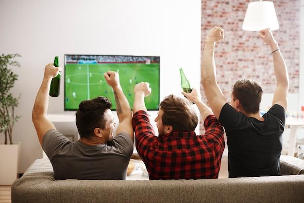 Achteraanzicht van mannen die naar een wedstrijd kijken en een voetbalwedstrijd juichen