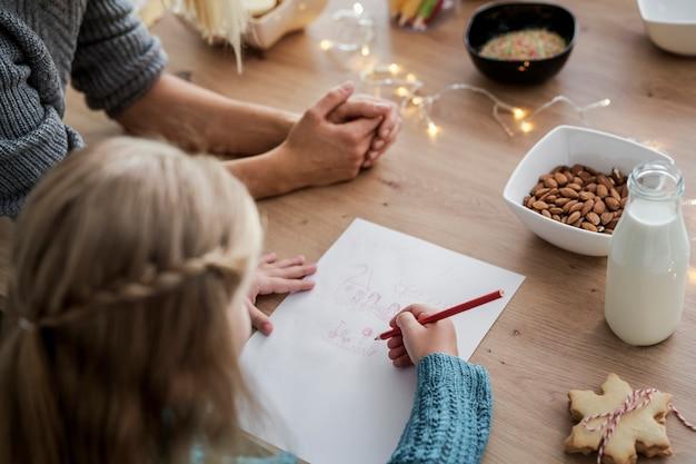 Achteraanzicht van meisje dat een brief schrijft aan de kerstman
