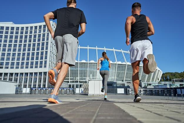 Achteraanzicht van meisje en mannen die naar het stadion rennen