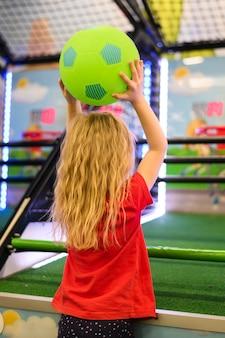 Achteraanzicht van meisje houdt van bal