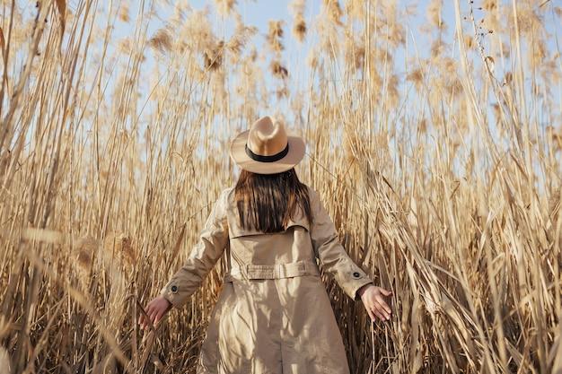 Achteraanzicht van meisje in trenchcoat en hoed in hoog pampagras met blauwe lucht op de achtergrond