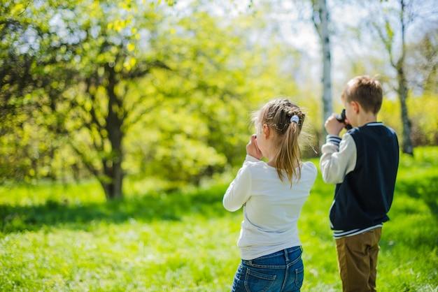 Achteraanzicht van meisje met camera en jongen met verrekijker