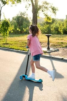 Achteraanzicht van meisje met roze t-shirt op scooter