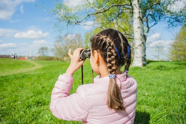 Achteraanzicht van meisje met verrekijker