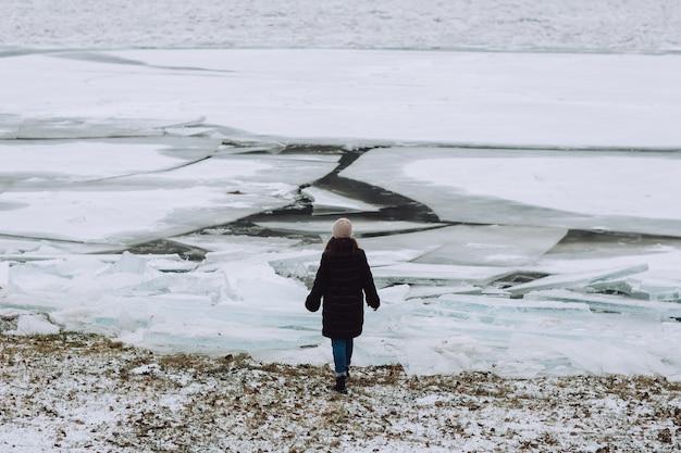 Achteraanzicht van meisje op de achtergrond van de rivier van de winter met gebarsten ijs. landschap met bevroren rivier.