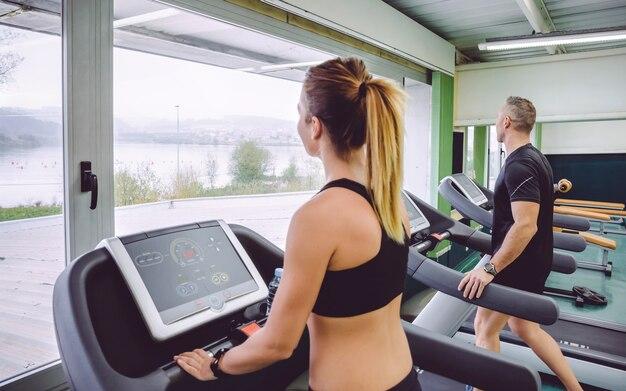 Achteraanzicht van mensen die opwarmen boven de loopband in een trainingssessie in het fitnesscentrum