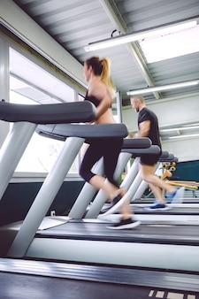 Achteraanzicht van mensen in beweging tijdens een loopbandtraining in het fitnesscentrum