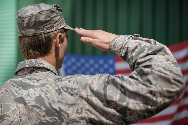 Achteraanzicht van militaire soldaat groet amerikaanse vlag in laarskamp