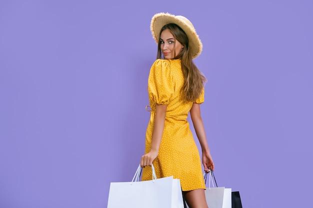 Achteraanzicht van mode jonge vrouw houdt pakketten vast na het winkelen korting zwarte vrijdag verkoop concept