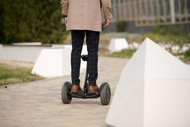 Achteraanzicht van moderne jongeman in broek en trenchcoat staande op gyroscoop en verhuizen naar businesscentrum in de ochtend
