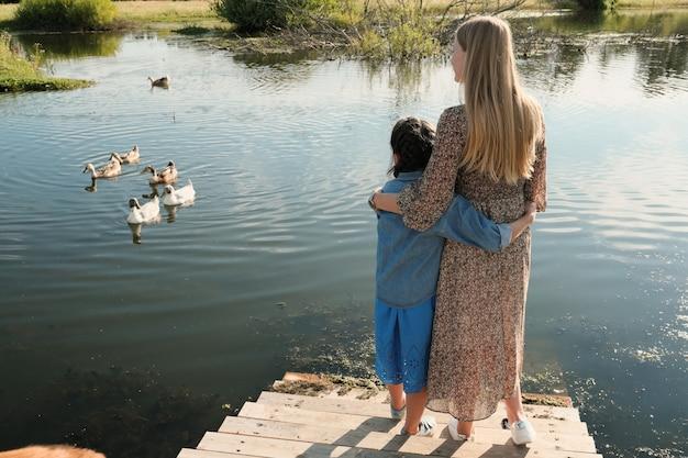 Achteraanzicht van moeder en dochter die elkaar omhelzen terwijl ze op de brug staan en buiten kijken naar de zwanen op de rivier