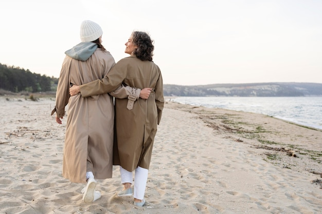 Achteraanzicht van moeder en dochter die op het strand lopen