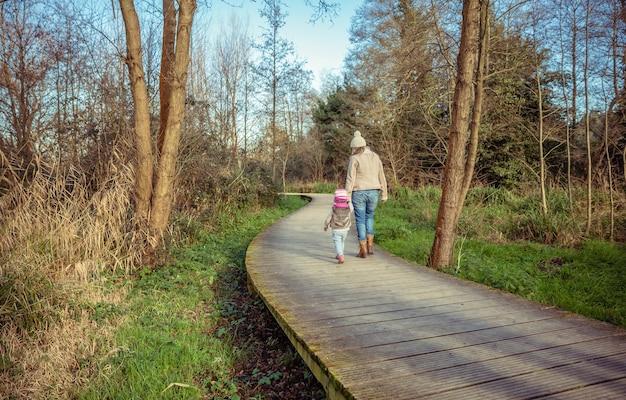 Achteraanzicht van moeder en dochter die samen hand in hand lopen over een houten pad naar het bos