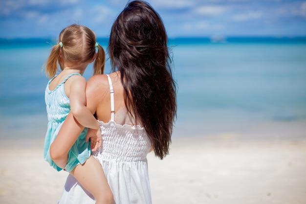 Achteraanzicht van moeder en zijn kleine dochter kijken op de zee tropisch strand
