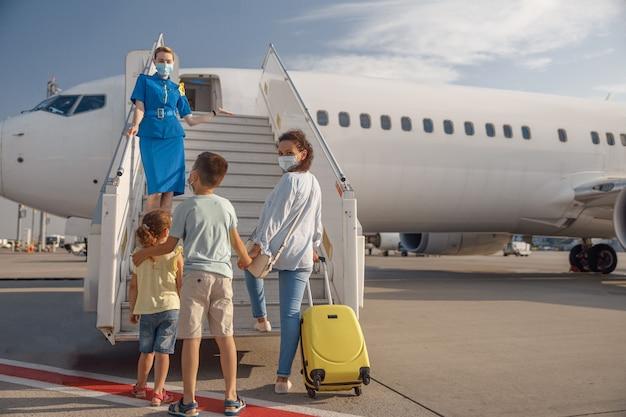Achteraanzicht van moeder met twee kleine kinderen met een beschermend masker die overdag aan boord gaan van het vliegtuig, klaar voor zomervakanties. mensen, reizen, vakantieconcept