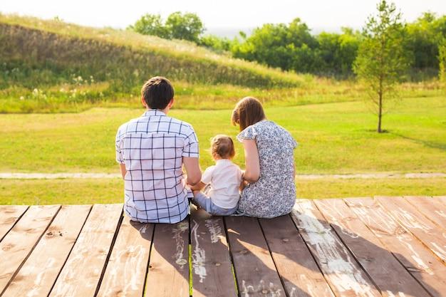 Achteraanzicht van moeder, vader en zoon die samen buiten zitten