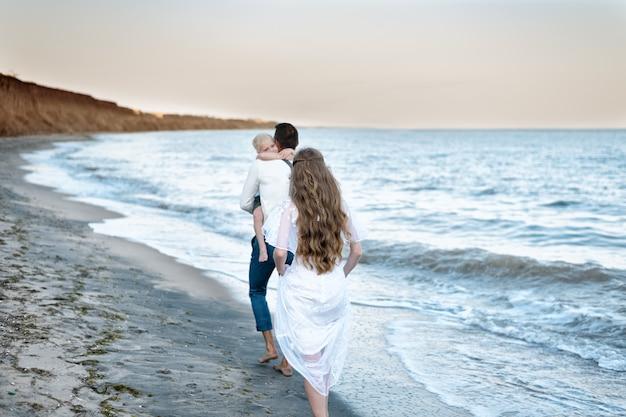 Achteraanzicht van moeder, vader en zoon wandelen in zee. bruiloft op zee met kinderen