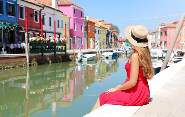 Achteraanzicht van mooi meisje in een rode jurk zitten en kijken burano oude kleurrijke stad in venetië, italië
