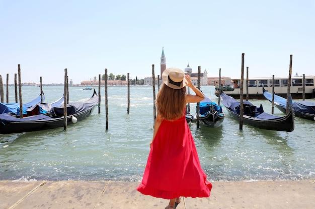 Achteraanzicht van mooi meisje in lange rode jurk genieten van uitzicht op de lagune van venetië