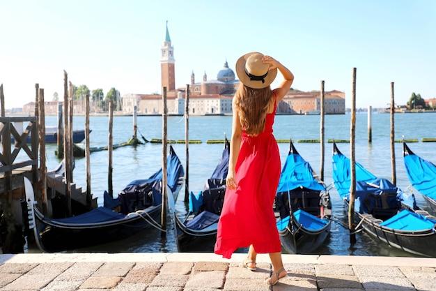Achteraanzicht van mooi meisje in rode jurk wandelen in venetië met afgemeerde gondels
