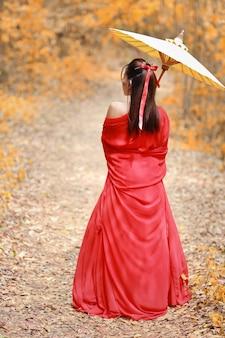 Achteraanzicht van mooie aziatische vrouw in rode krijger chinees kostuum met oude paraplu