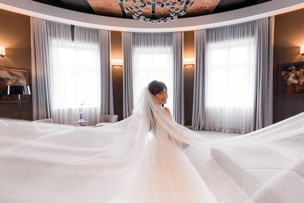 Achteraanzicht van mooie brunette bruid met een lange sluier kijkt over haar schouder naar de camera in hotelkamer