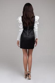 Achteraanzicht van mooie jonge vrouw die elegante jurk draagt en op een grijze achtergrond staat. schoonheid en mode concept
