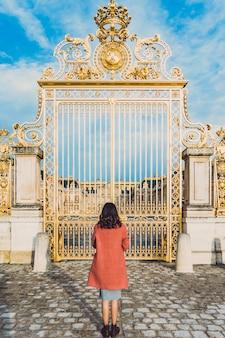 Achteraanzicht van mooie jonge vrouw die zich voordeed bij de gouden poorten van het paleis van versailles in parijs, frankrijk.