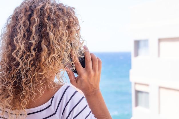 Achteraanzicht van mooie krullende vrouw tijdens het gebruik van de telefoon. blauwe zee op de achtergrond. vrouwelijk model met kopieerruimte