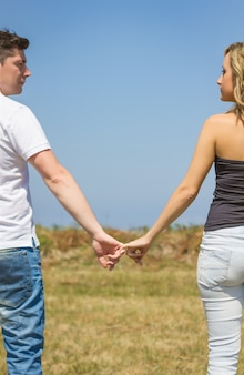 Achteraanzicht van mooie liefdespaar hand in hand buiten over een zomer veld achtergrond