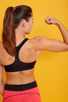 Achteraanzicht van mooie sterke gespierde vrouw toont haar biceps en armspieren, slanke vrouw met paardenstaart jurken zwarte top en legging, poseren geïsoleerd over gele studio