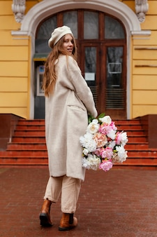 Achteraanzicht van mooie vrouw met boeket bloemen buitenshuis