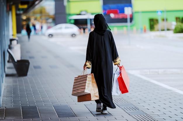 Achteraanzicht van moslimvrouw in traditionele slijtage buiten wandelen met boodschappentassen in handen. mode is voor iedereen. diversiteit concept.