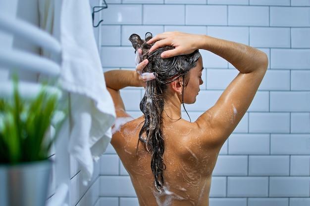Achteraanzicht van naakte vrouw haar met shampoo wassen tijdens het nemen van een douche