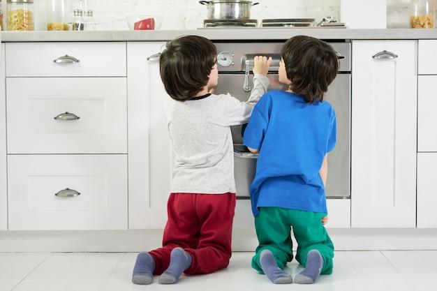 Achteraanzicht van nieuwsgierige kleine spaanse jongens, een tweeling kijkend naar het bakken van cake in de oven, gehurkt in de keuken. kinderen, kookconcept