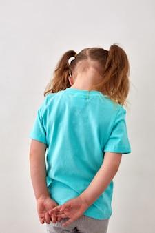 Achteraanzicht van onherkenbaar boos meisje met paardenstaarten gekleed in een blauw t-shirt dat tegen een witte muur staat