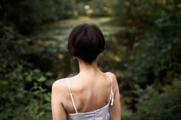 Achteraanzicht van onherkenbare jonge vrouw met kort haar en slank lichaam poseren buitenshuis, staande voor vijver met haar rug naar de camera.