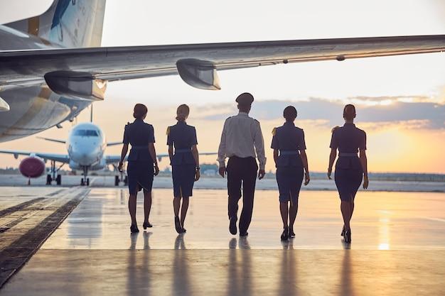 Achteraanzicht van onherkenbare mensen die buiten naar het vliegtuig gaan