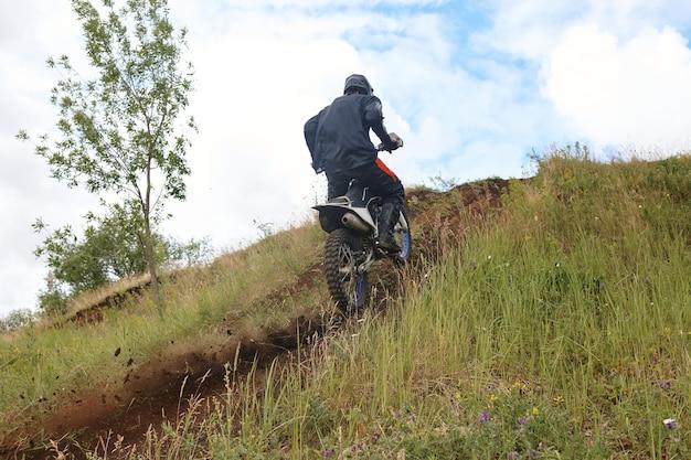 Achteraanzicht van onherkenbare motorrijder in jas klimmen heuvel trail buitenshuis