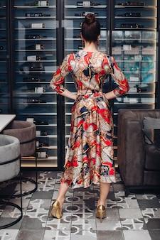 Achteraanzicht van onherkenbare volwassen vrouw met donker haar in knot, gekleed in zijden avondjurk en gouden hakken die haar handen op de taille houden. poseren tegen wijnflesplanken in wijnmakerijboetiek.