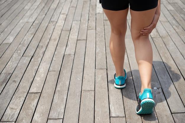 Achteraanzicht van onherkenbare vrouwelijke hardloper in blauwe sportschoenen die op een houten pier staat en pijnpunt aanraakt terwijl ze pijn voelt onder de knieschijf
