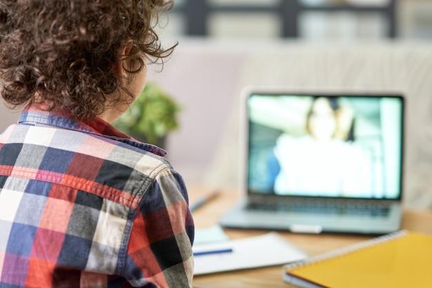 Achteraanzicht van online onderwijs van latijnse schooljongen die aantekeningen maakt met online les met behulp van laptop
