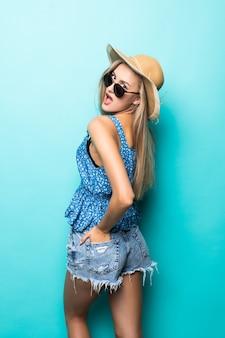 Achteraanzicht van opgewonden glimlach vrouw stro zomer hoed op blauwe achtergrond.