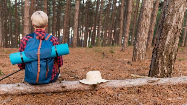 Achteraanzicht van oudere toeristische vrouw in het bos met rugzak