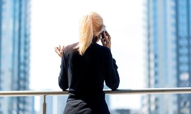 Achteraanzicht van oudere zakenvrouw buiten op een telefoontje