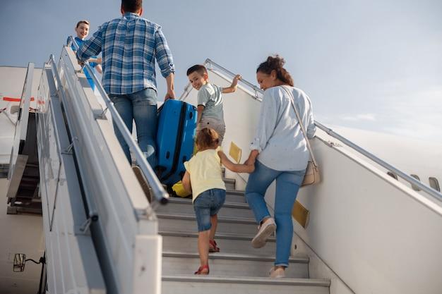 Achteraanzicht van ouders met twee kinderen die aan boord gaan, overdag aan boord van het vliegtuig, klaar voor zomervakanties. mensen, reizen, vakantieconcept