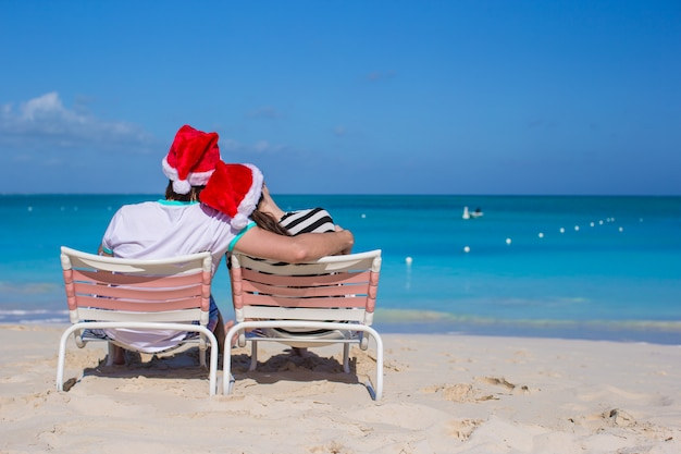 Achteraanzicht van paar in santa hoeden genieten van strandvakantie