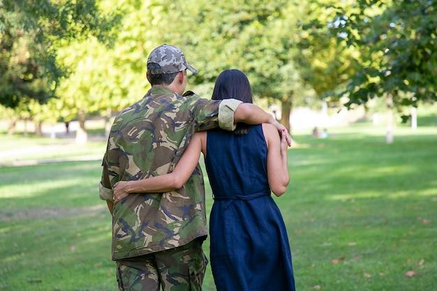 Achteraanzicht van paar knuffelen en samen wandelen op gazon in park. man met camouflage uniform, zijn vrouw omhelzen en genieten van zonnige dag. familiereünie, weekend en thuiskomst concept