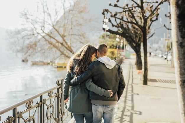 Achteraanzicht van paar knuffelen en wandelen aan de oever van het meer van lugano, zwitserland.